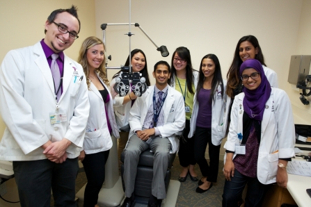 """A doctor in a freshly starched white clinic jacket is a commanding figure; taking his or her best care of a patient, a doctor can seem like a rock star to the uninitiated and aspiring pre-optometry student."" MBKU students surround Dr. Raman Bhakhri for a great shot!"